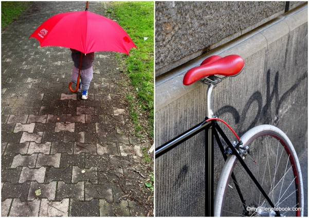 a child with red umbrella, red and black bicycle