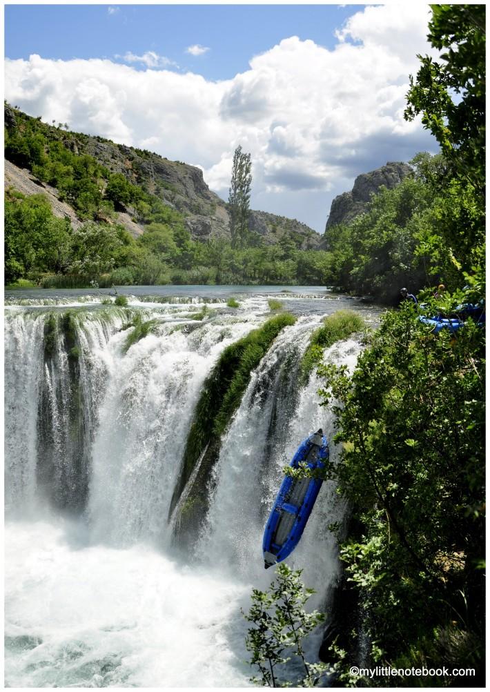 blue kayak falling down the waterfall on zrmanja river
