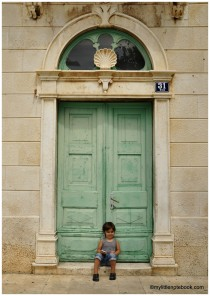 Little boy in front of a big light green door
