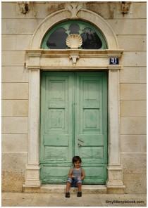 Little boy in front of a big light green door
