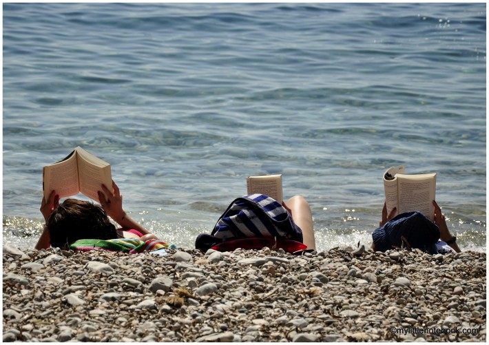 three women reading books at a beach