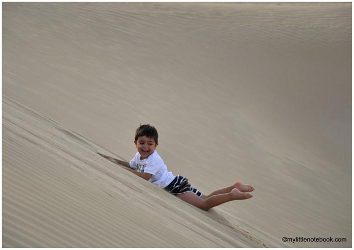 boy sliding on a dune