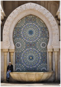 Man sitting in front of a mosque in Morocco